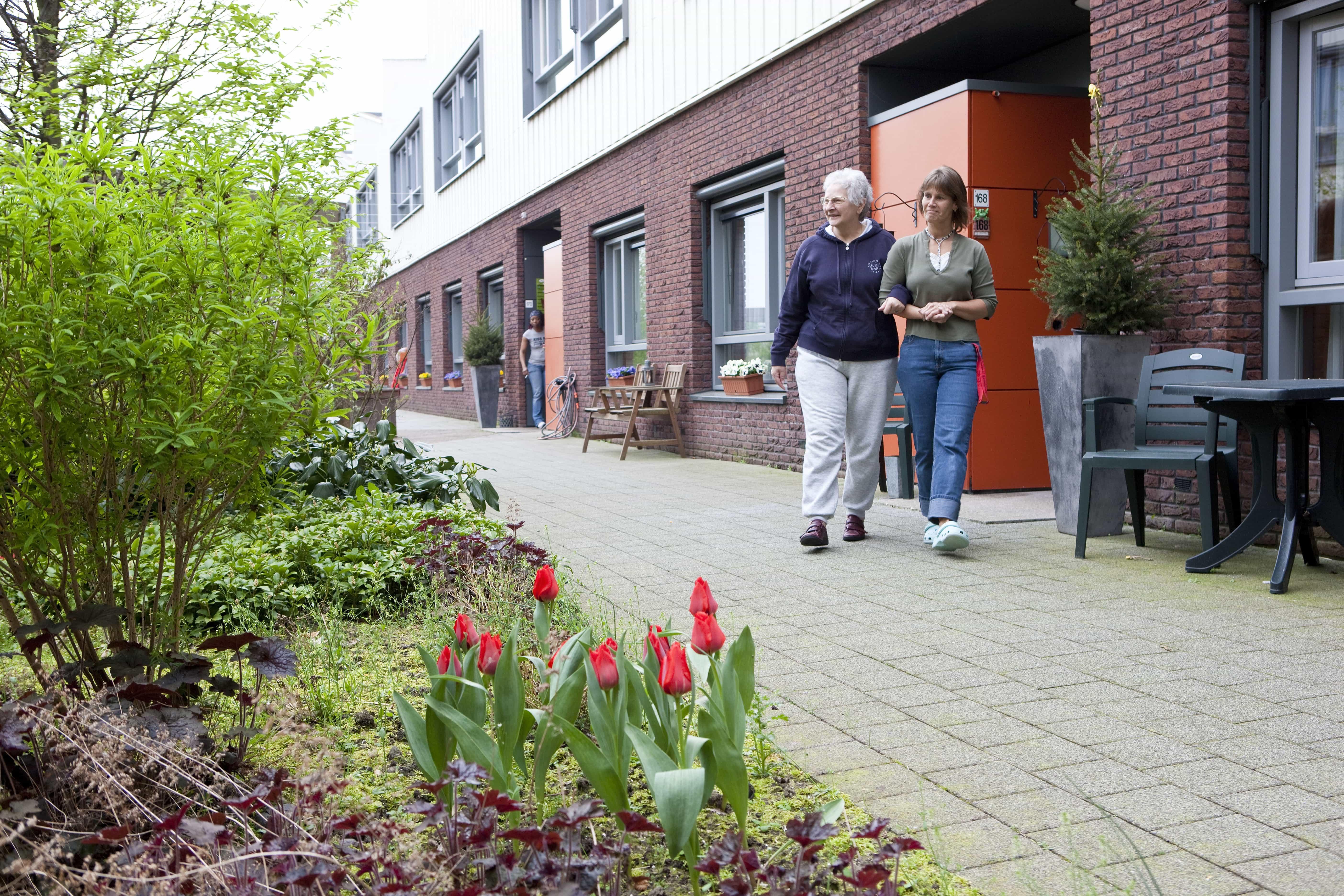 Oudere vrouw wandelt buiten, in een straat met tuin, samen met verzorgster