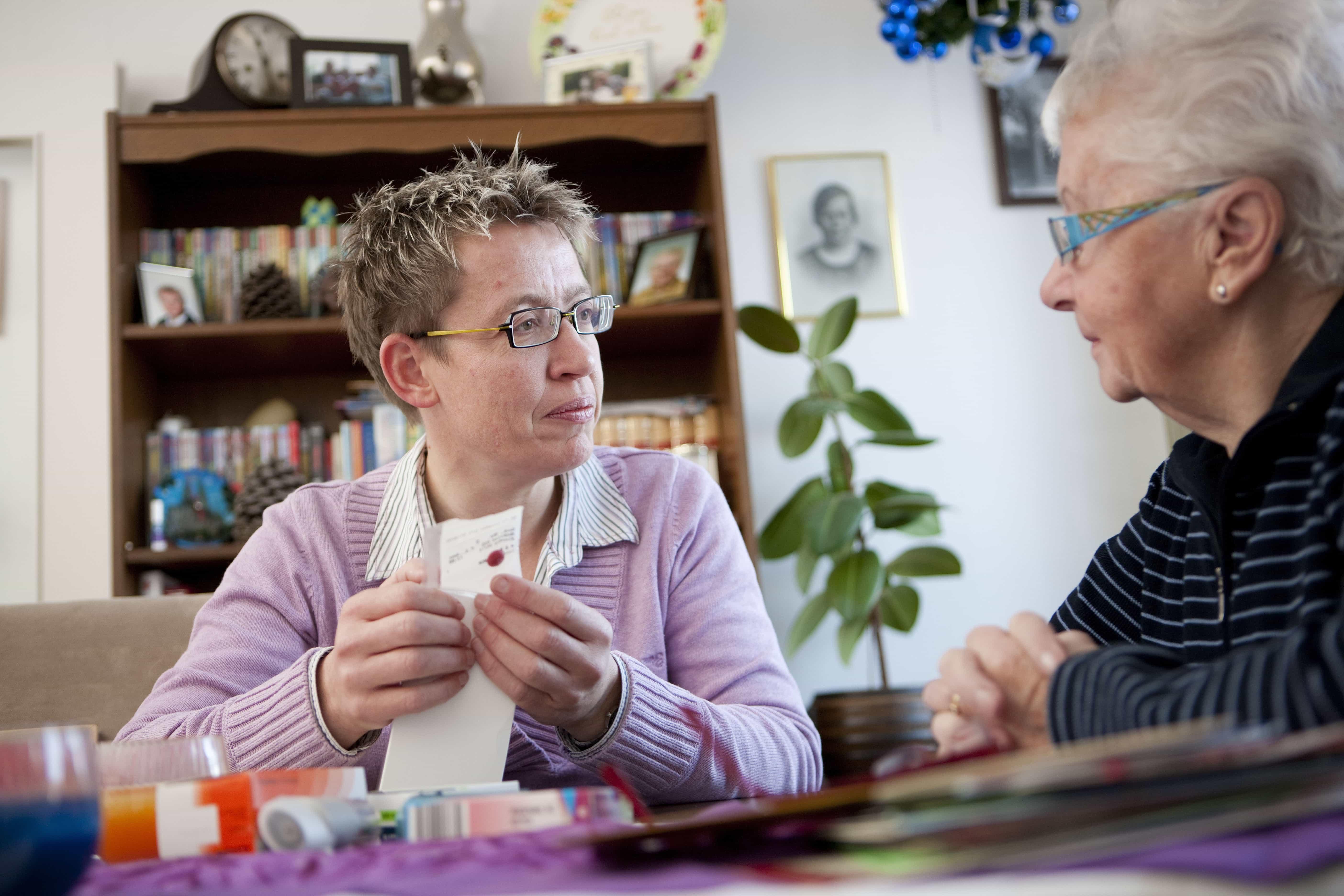 Oudere vrouw aan tafel met apotheker