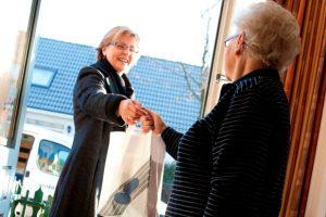 Apotheker brengt medicijnen langs bij oudere vrouw