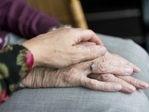 De handen van een ouder persoon worden vast gehouden
