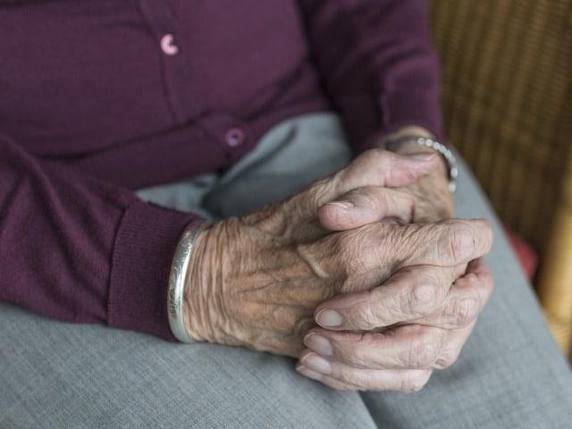 Zittende dame met gevouwen handen