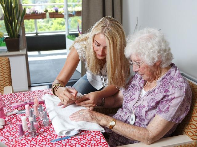 Vrouw lakt de nagels van een oudere dame