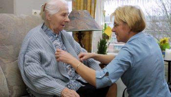 Verzorgende helpt een oudere dame met aankleden.